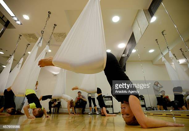 Women and children practice yoga with hammock and hang in the air in a sports center in Moscow Russia on 24 July 2014
