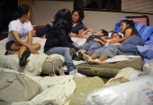 Women and children rest on matresses at a shelter for tornado survivors set up at the Holy Spirit Catholic Church April 30 2011 in Tuscalosa Alabama...