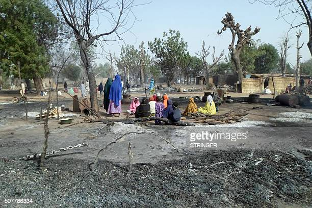 Women and children sit among burnt houses after Boko Haram attacks at Dalori village on the outskirts of Maiduguri in northeastern Nigeria on January...
