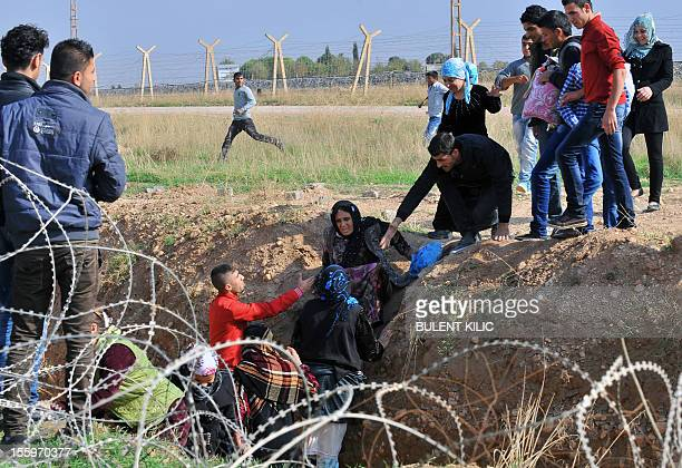 Women and children Syrian nationals climb into a ditch leading to a barbed wire fence to cross the border between the Syrian town of Ras alAin and...