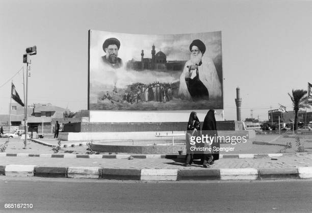 Women and children walk past a painted mural at the entrance to Sadr City formerly known as Saddam City The mural depicts the uncle of Moqtada alSadr...