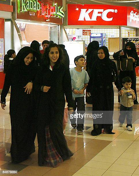 Women and children walk past food chains inside a shopping mall in the Saudi capital Riyadh on February 18 2009 Saudis have cheered King Abdullah's...