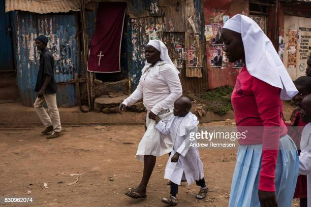 Women and children walk to church in the Kibera slum on August 13 2017 in Nairobi Kenya A day prior demonstrations turned violent in some areas...
