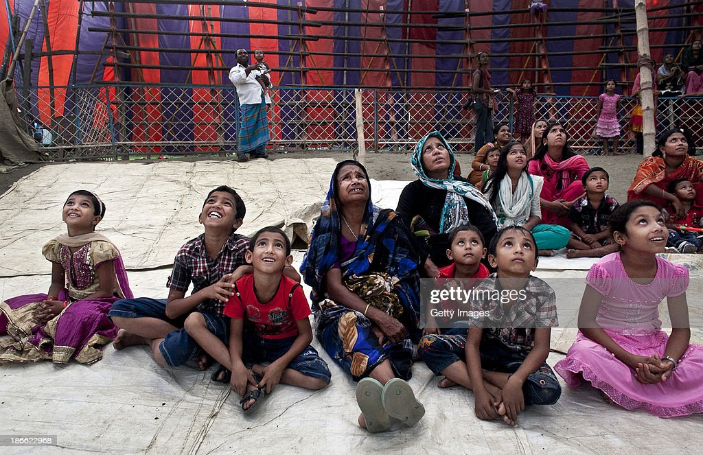 Women and children watch a performance at the Olympic Circus, November 1, 2013 in Jamsha, Bangladesh. Generations of low income families are born into circuses with rarely the hope of ever working in different profession or escaping the harsh realities of the circus. The children, often very young, are trained to be full working members usually without the opportunity for an education. As modernization slowly takes over landscape of Bangladesh, the circus is a dying art form and is moving further and further away from mainstream entertainment.