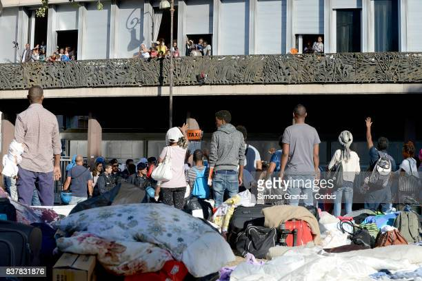 Women and children who have been allowed to temporarily remain in an occupied building stand with gas cylinders on their balconies and protest...