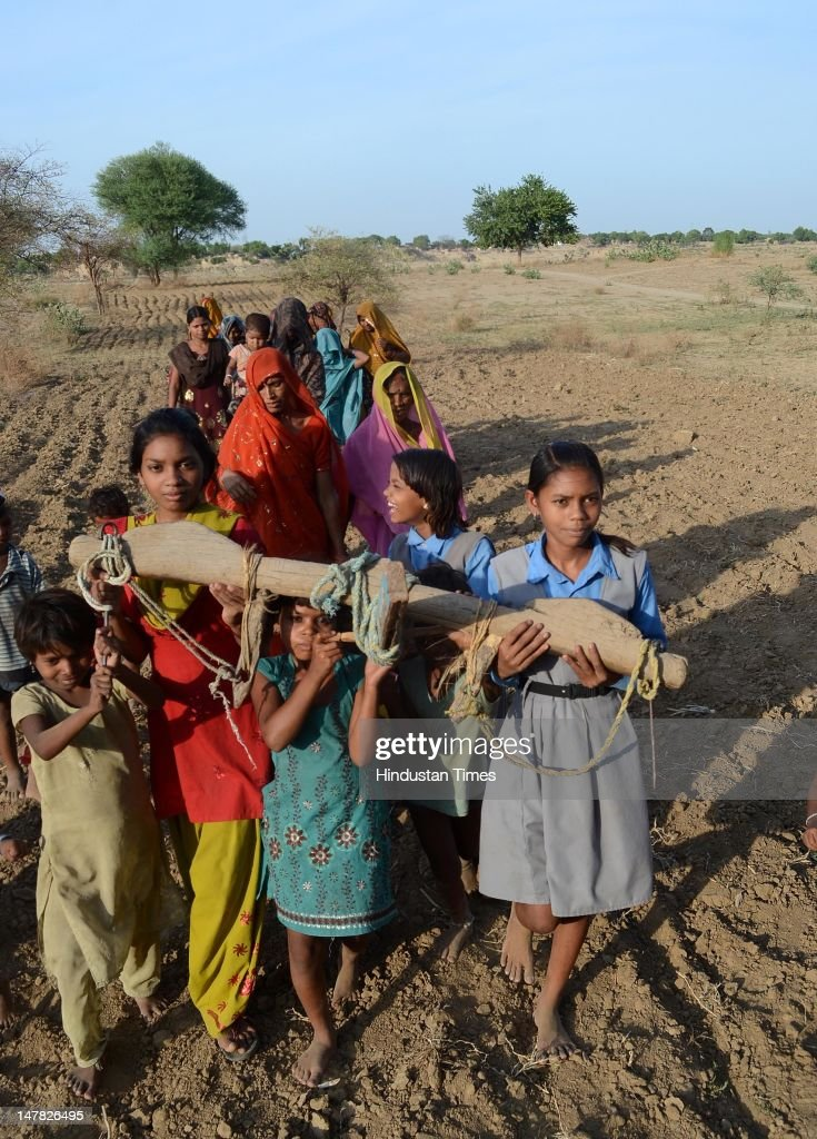Women and girls ploughing the dry fields as part of 'Har Padoury' Ritual to please the rain god at Benipur village on July 3, 2012 in Allahabad, India. Scant rainfall in the region of Eastern Uttar Pradesh has left farmers worried about their paddy crops which heavily depend on Monssons.