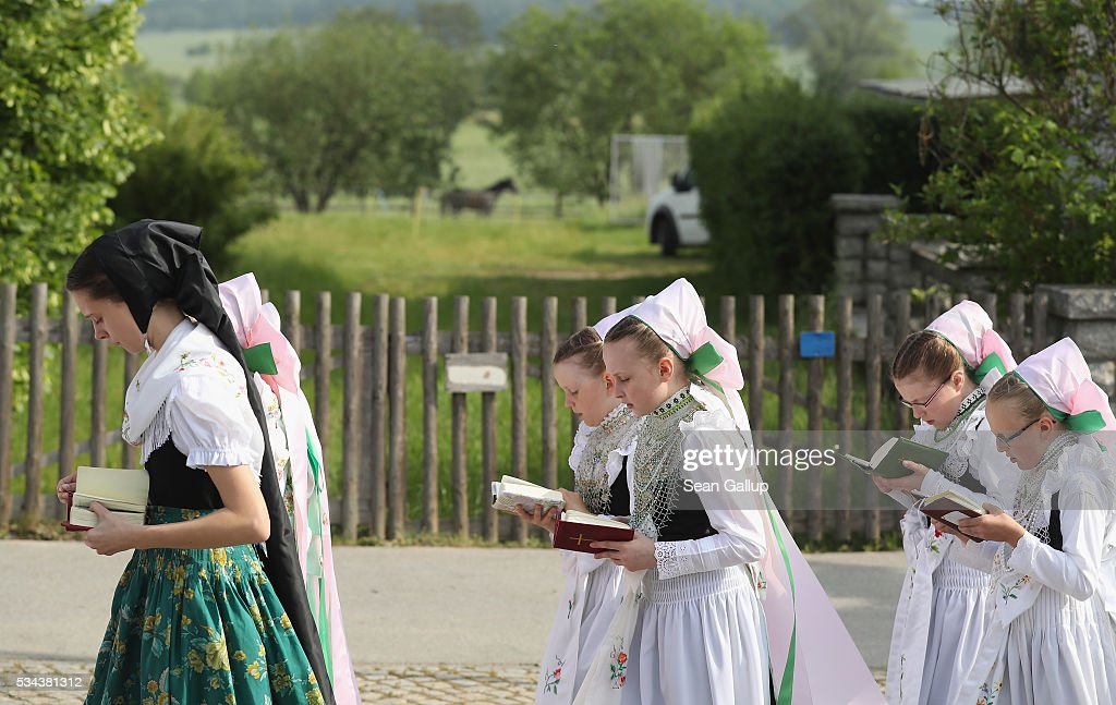 Women and girls wearing traditional Sorbian festive dress participate in the annual Sorbian Corpus Christi procession through the village center as they walk past a farm and a horse on May 26, 2016 in Crostwitz, Germany. Sorbians are a Slavic minority in southeastern Germany who speak a language similar to Czech and Polish. Sorbian is still taughet in some schools in the region and a lively tradition of Sorbian literature, theater and folk culture has survived.