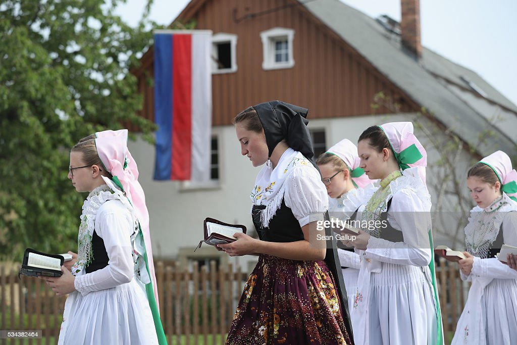 Women and girls wearing traditional Sorbian festive dress walk past a flag adorned with a Sorbian flag as they participate in the annual Sorbian Corpus Christi procession through the village center on May 26, 2016 in Crostwitz, Germany. Sorbians are a Slavic minority in southeastern Germany who speak a language similar to Czech and Polish. Sorbian is still taughet in some schools in the region and a lively tradition of Sorbian literature, theater and folk culture has survived.