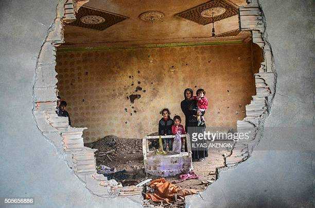 TOPSHOT A women and her children stand in the ruins of battledamaged house in the Kurdish town of Silopi in southeastern Turkey near the border with...