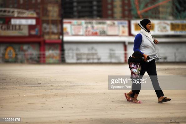 A women and her daughter walk along a sandswept beach at Coney Island following heavy rain and winds from Hurricane Irene on August 28 2011 in the...