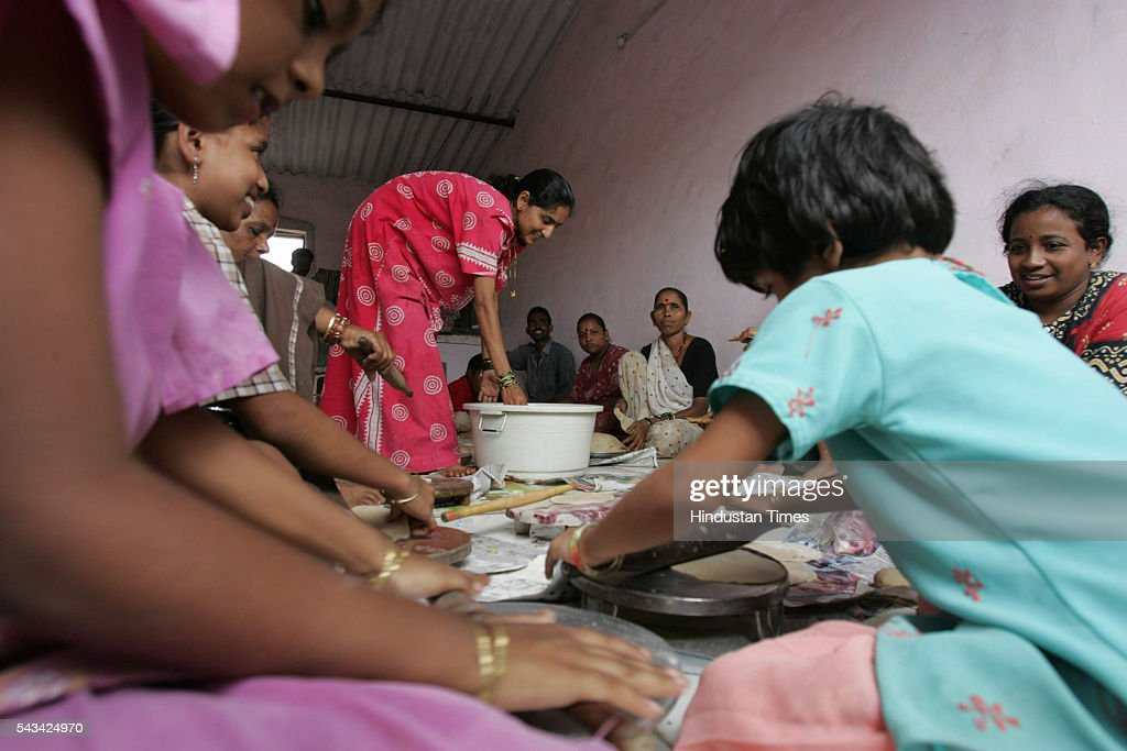 Women and kids making poories and bhaji for the people affected by the flood at Diva on August 1, 2005 in Mumbai, India.