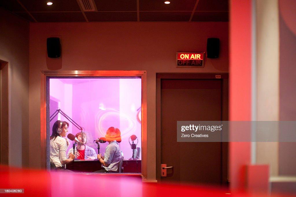 Women and man broadcasting in recording studio