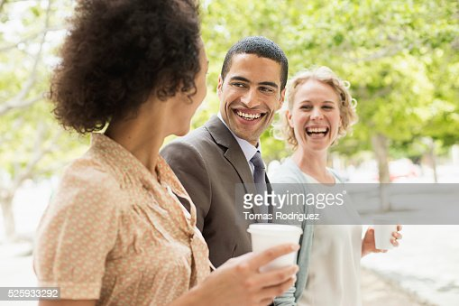 Women and man having coffee break in park : Foto de stock