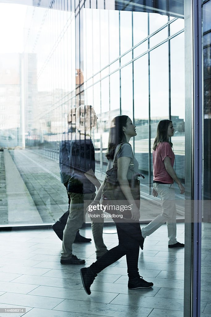 Women and men walking behind glass. : Stock Photo