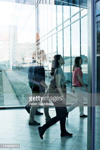 Women and men walking behind glass. : Stock Photo