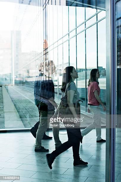Women and men walking behind glass.