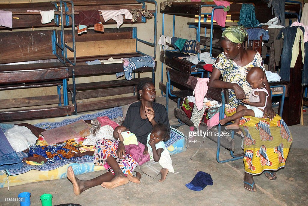 Women and their children take shelter in a school on August 30, 2013 after flash floods in Bamako. At least 23 people have been killed in flash floods caused by torrential rain in the Malian capital Bamako, a government official said today. Thousands were also made homeless as the Niger river burst its banks, destroying around 100 houses in several hours of heavy rain on Wednesday in the city of around two million people, said Alassane Bocoum, the national director of social development. AFP PHOTO / HABIBOU KOUYATE