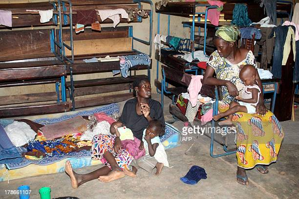 Women and their children take shelter in a school on August 30 2013 after flash floods in Bamako At least 23 people have been killed in flash floods...