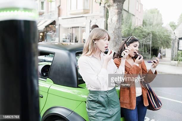Women applying lipstick on city street