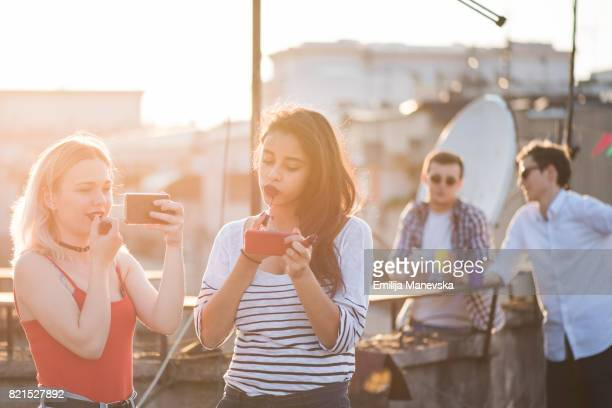 Women applying make up at the roof top party