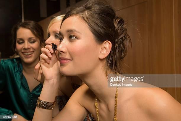 Women applying make up.