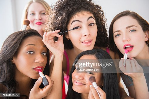 Women applying makeup in mirror