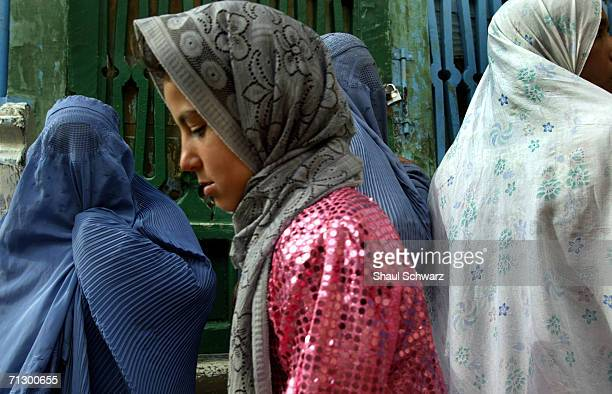 Women are covered with burkas as a younger lady walks by wearing a scarf in a shrine on April 11 2004 in Herat Afghanistan Since the fall of the...