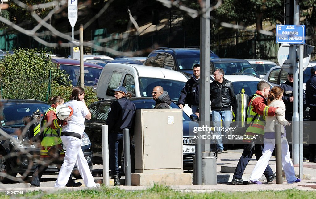 Women are escorted by policemen and firefighters as they leave a dental surgery during an intervention of French special police forces (GIPN), on March 19, 2013 in Marseille, southern France, after a female dentist was shot dead by a 71-year-old patient who was himself killed during the subsequent police intervention. A police source said the man had been in dispute with the practice over an unpaid bill of around 100 euros.