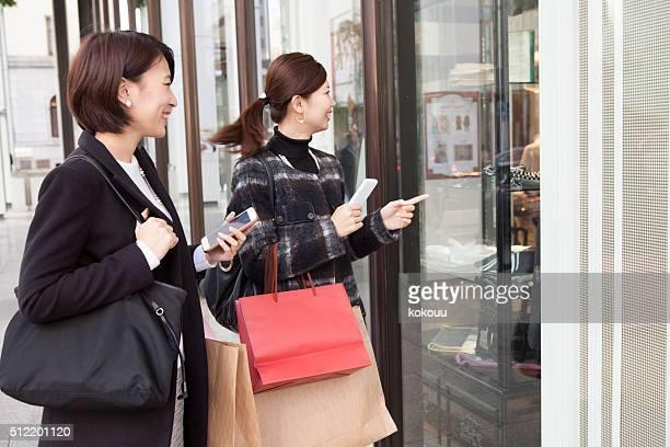 女性が見られる、ショップのウィンドウにお尋ねください。