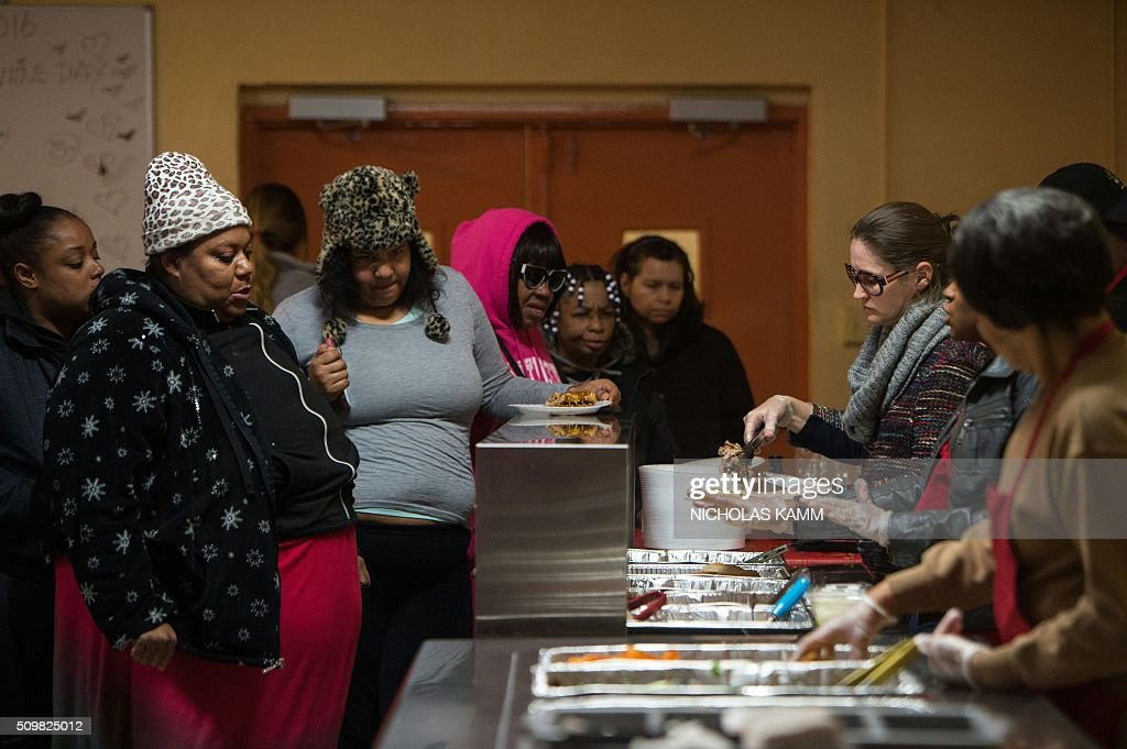 Women are served food during a Spa Day for homeless and at-risk women organized by ThriveDC, an organization fighting homelessness, in Washington, DC, on February 12, 2016. Recent research published in the American Journal of American Health finds that unstably-housed women experience dramatically higher incidence of physical, sexual and emotional violence. / AFP / Nicholas Kamm