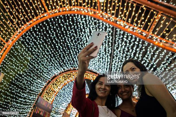 Women are take a photo next to Christmas decorations in Cali Colombia on December 11 2017 / AFP PHOTO / LUIS ROBAYO