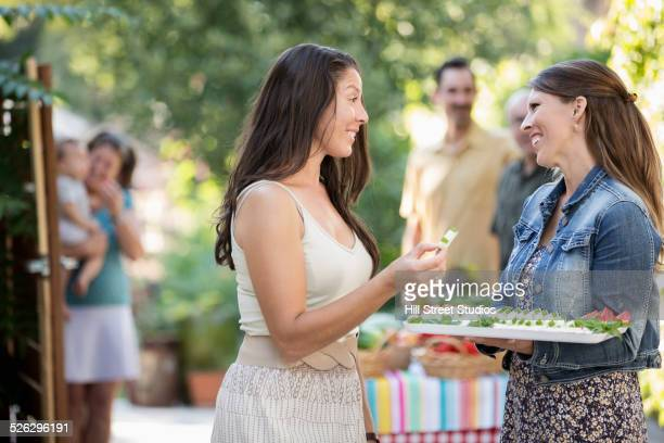Women arranging tray of snacks for backyard party