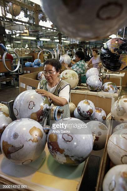 Women assembling world globes in factory