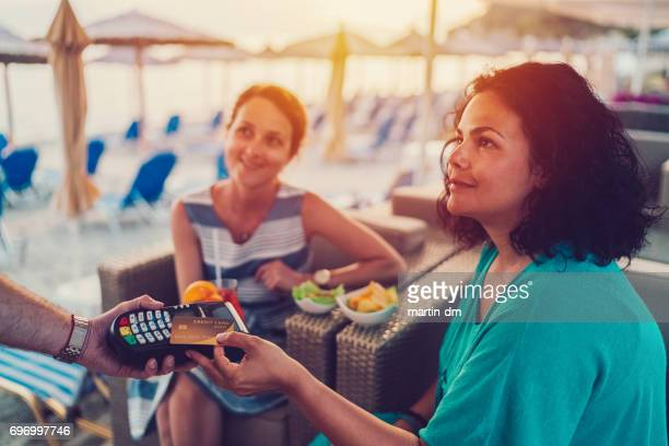 Women at beach holiday paying contactless with credit card