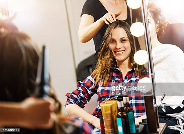 Women at beauty parlour having haircut and make up treatment