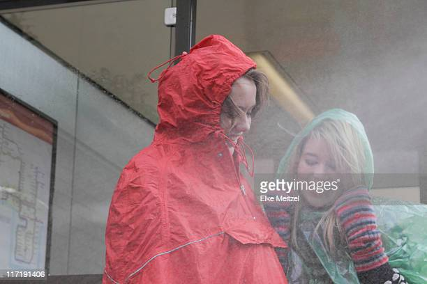 2 women at bus stop in the rain