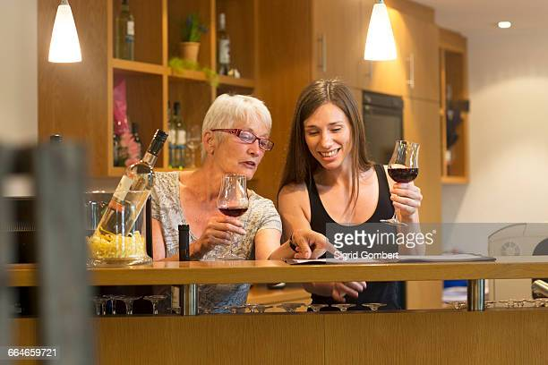 Women at counter in wine bar holding wine glasses chatting