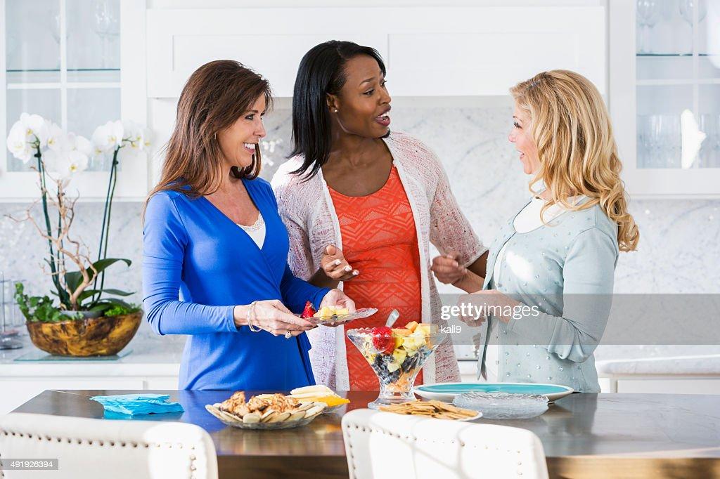 Mulheres com refeição na cozinha tendo conversa : Foto de stock