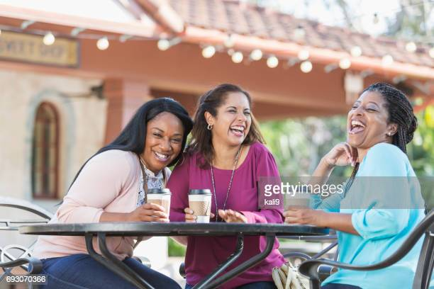 Women at sidewalk cafe drinking coffee, laughing