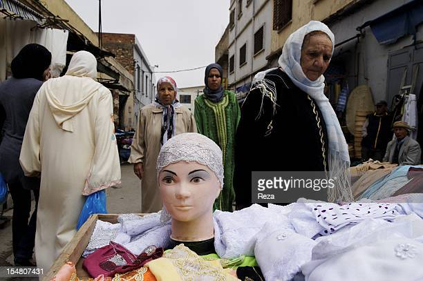 Women at the market Madina Jadida wearing a djellaba and a scarf in front a table full of scarves