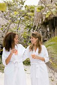 Women at tropical resort in robes