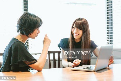Donne al lavoro, discutere e usando il computer portatile