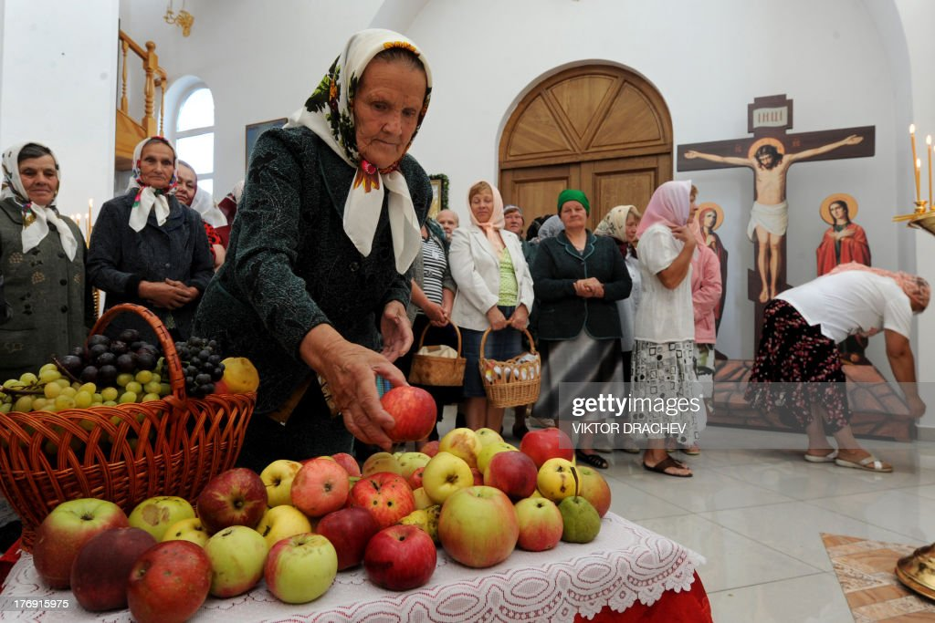 Women attend a religious service marking the Transfiguration of Jesus holiday also known as Yablochny Spas (Apple Salvation) inside an Orthodox cathedral in the ancient in Belarus town of Turov, some 250 km south of Minsk, on August 19, 2013. AFP PHOTO / VIKTOR DRACHEV