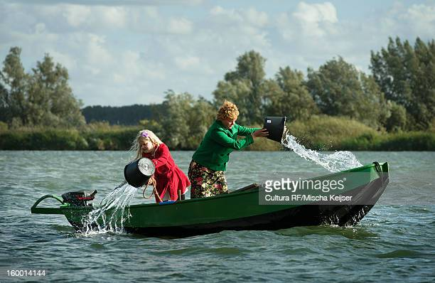 Women bailing water out of boat in lake