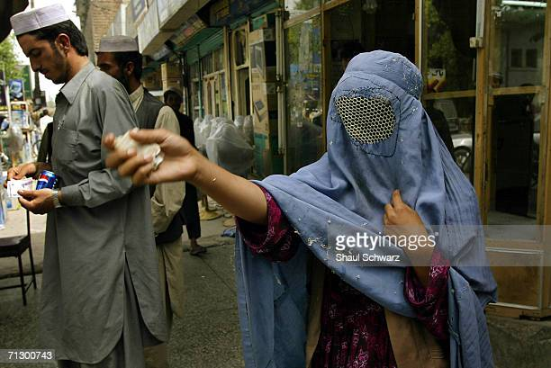 A women begs for money on the main street of Jalalabad on April 20 2004 in Jalalabad Afghanistan Since the fall of the Taliban there is no law...