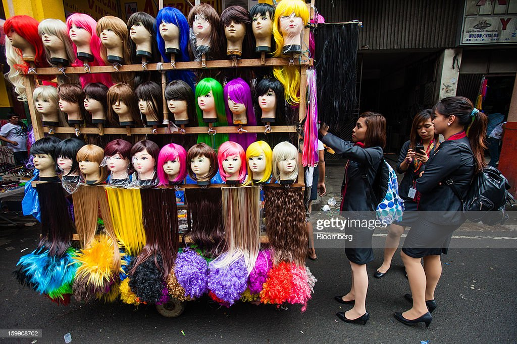 Women browse a stall selling wigs and hair extensions at the Divisoria market in Manila, the Philippines, on Tuesday, Jan. 22, 2013. Philippine government bonds advanced on speculation the central bank will hold its benchmark interest rate at a record low at a meeting tomorrow, supporting demand for the nation's debt. Photographer: Julian Abram Wainwright/Bloomberg via Getty Images