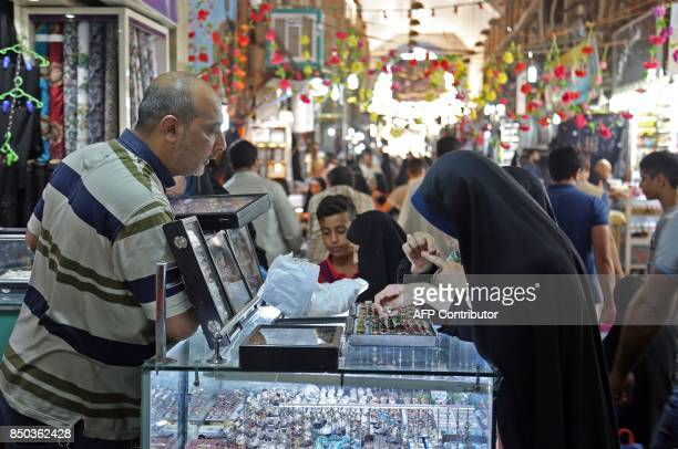 Women browse for rings at a stall oustide a jeweller's shop in the main market of Iraq's holy city of Najaf on September 13 2017 Strategically...