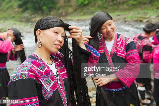 Women brush and style long hair in Longji village, China. : Stock Photo