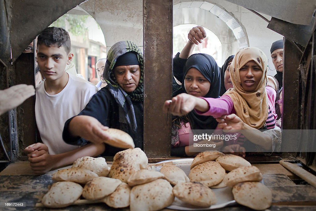 Women buy bread from the window of a bakery in Cairo, Egypt, on Monday, May 20, 2013. Egypt will curb wheat imports by 31 percent to 8 million metric tons in 2012-13, still enough to make it the world's biggest buyer, the U.S. Department of Agriculture estimates. Photographer: Shawn Baldwin/Bloomberg via Getty Images
