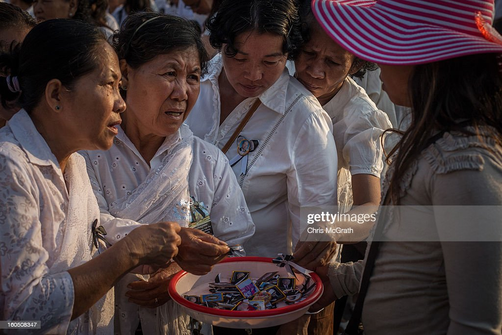 Women buy ribbons from a street vendor while they wait outside the Royal Palace before being allowed to enter the cremation site to pay their final respects to former King Norodom Sihanouk on February 2, 2013 in Phnom Penh, Cambodia. The former kings coffin was transported to the cremation site yesterday after being paraded through the capital in a lavish funeral procession. The cremation will take place on Monday the 4th of February, the funeral pyre will be lit by his wife and son King Norodom Sihamoni.